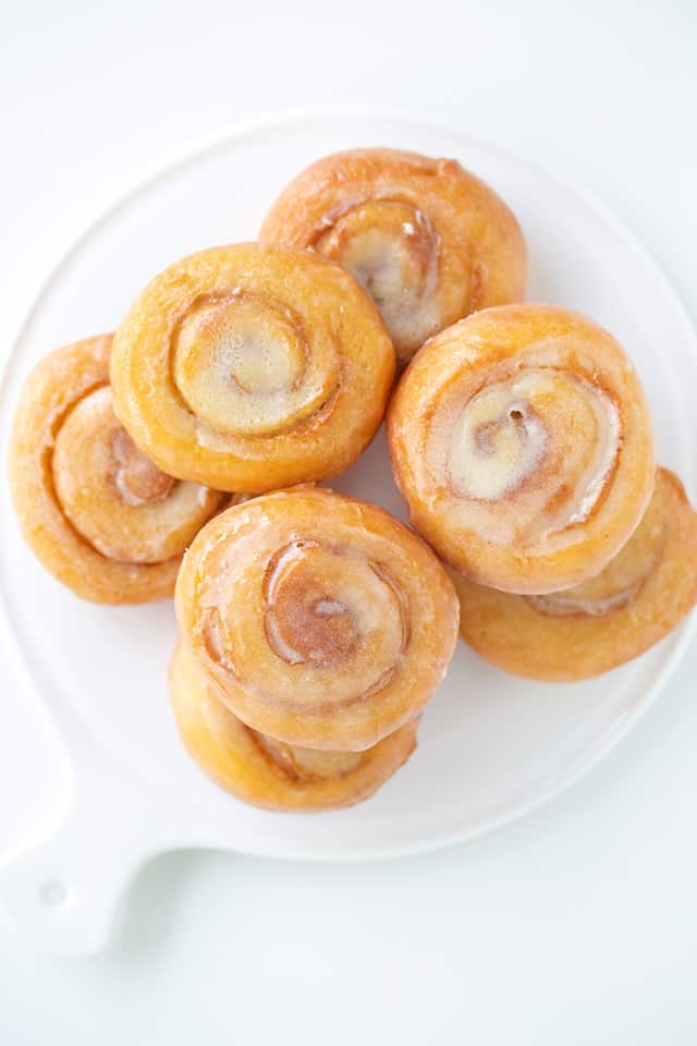 overhead view of honey buns stacked on a white plate