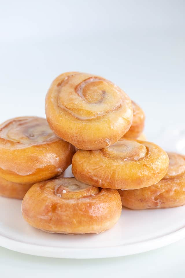 a pile of honey buns on a white plate
