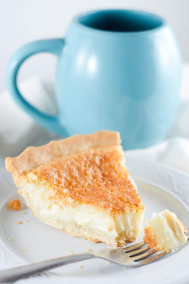 a slice of sugar cream pie with a forkful beside in on a white plate with a blue cup