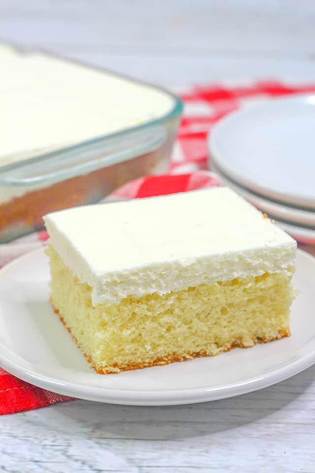 slice of depression cake on a small white plate with a red plain linen behind it