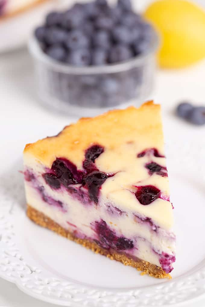 slice of blueberry cheesecake on a white plate with blueberries and lemon behind the plate