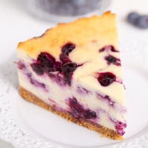 square image of a slice of cheesecake on a white lace plate with a couple of blueberries on the white background behind it