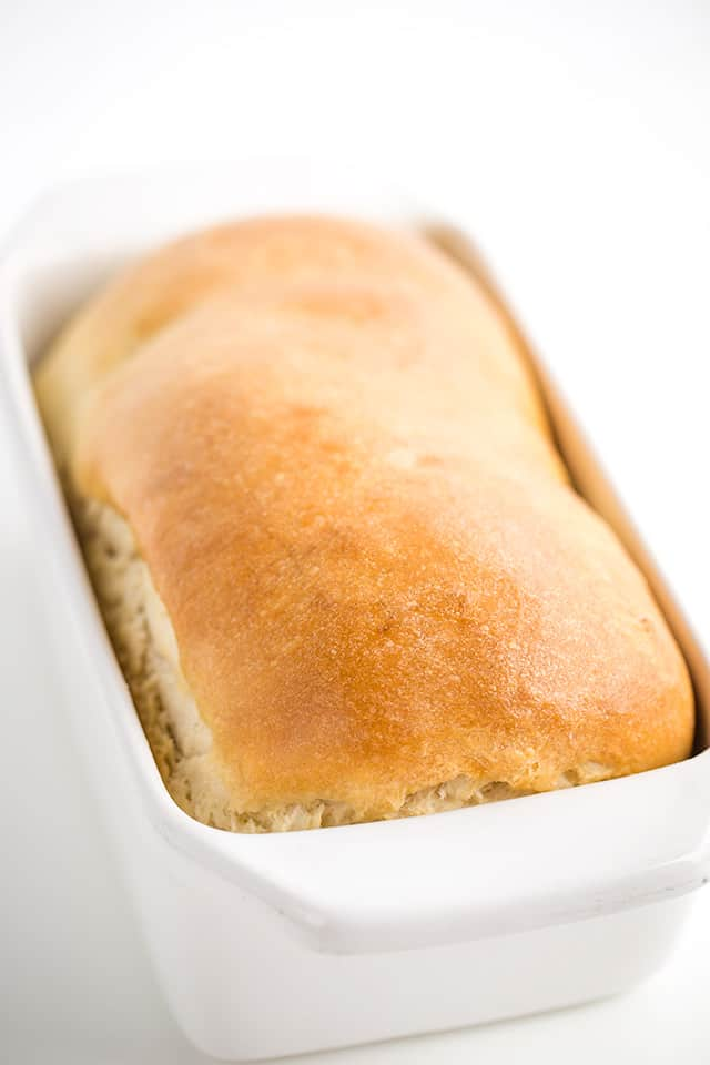 loaf of baked homemade bread in a white loaf pan