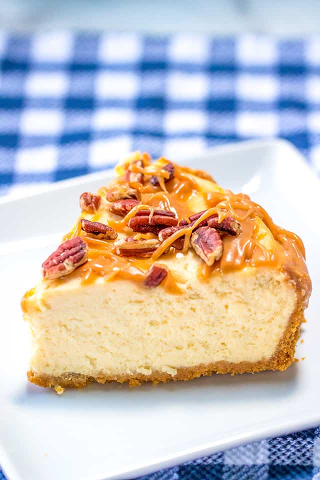 slice of salted caramel cheesecake on a white square plate with a blue plaid fabric
