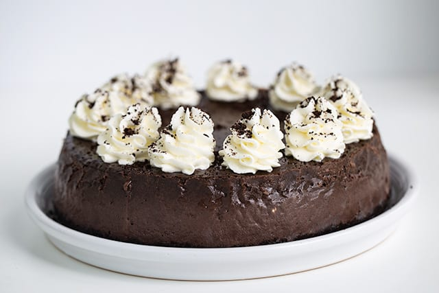 horizontal image of full cheesecake on a white serving plate with swirls of whipped cream