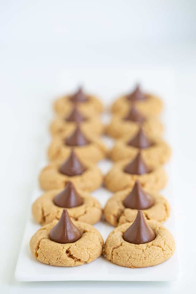 two rows of peanut butter kiss cookies on a long white platter with a white background