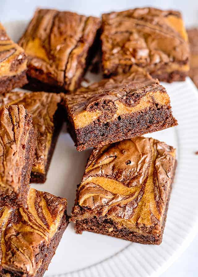 pumpkin brownies on a white plate with one propped up on another showing off the side of the brownie