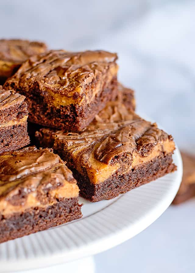 two pumpkin brownies in front of a white cake plate full of more brownies