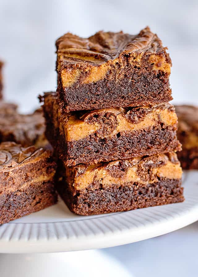3 pumpkin brownies stacked on a white cake plate