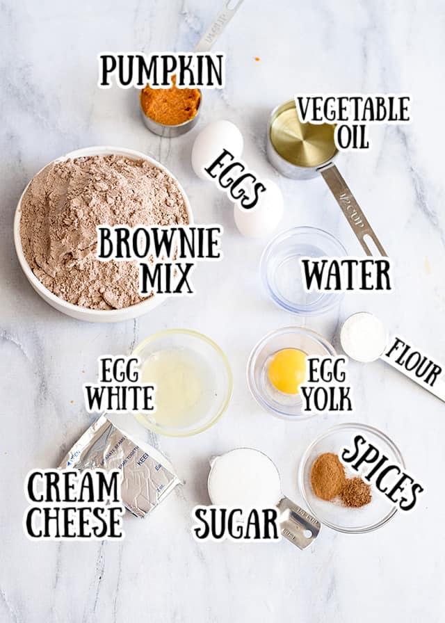 ingredients for pumpkin brownies on a marbled background with text