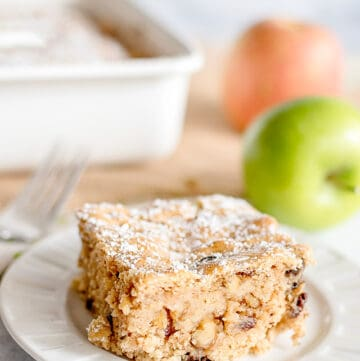 slice of applesauce cake on a white dessert plate with apples and a pan of cake behind it