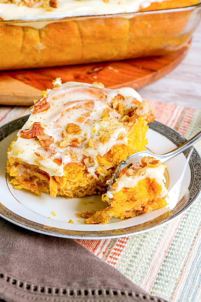 cinnamon roll on a small plate with a fork on the plate