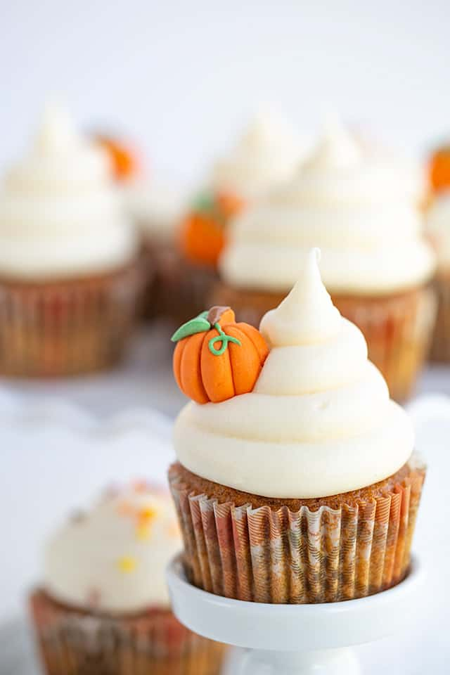 closeup of a pumpkin cupcake with a pumpkin decoration in the side of the cream cheese frosting