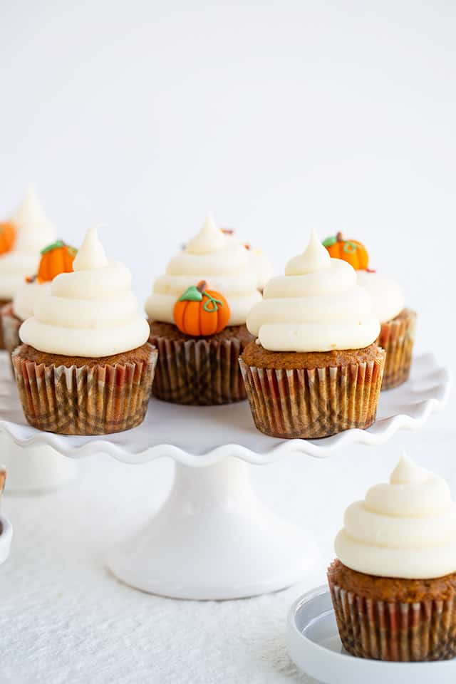 cupcakes with swirls of frosting on a white cake plate with a small white plate with a cupcake underneath