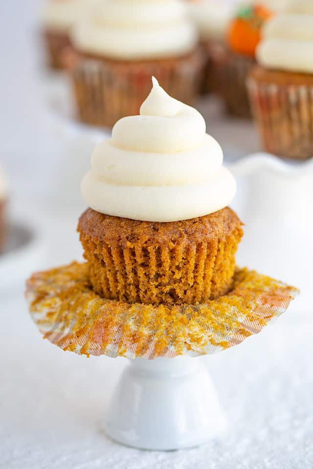 pumpkin cupcake with the wrapper peeled off on a white cupcake stand