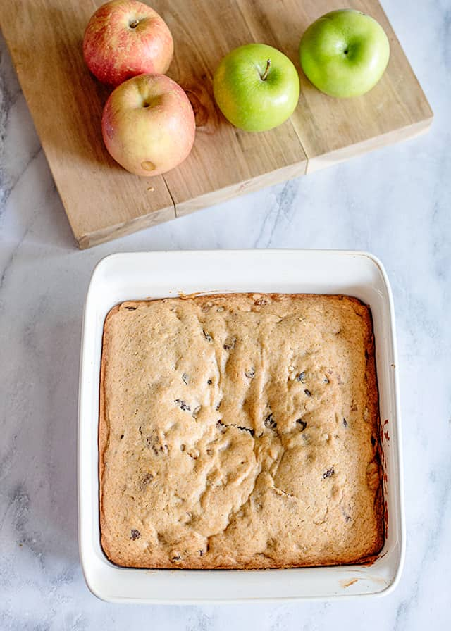 freshly baked applesauce cake in a white pan with a cutting board full of apples