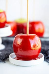 candy apple sitting on a round white plate with other apples behind it