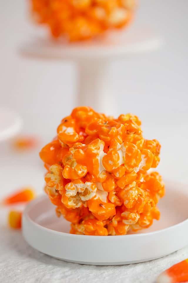 orange popcorn ball on a small white plate