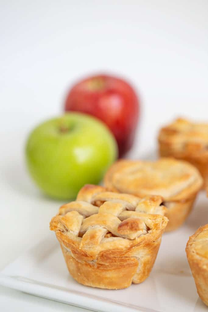 Mini apple pies in a white platter with green and red apples behind them
