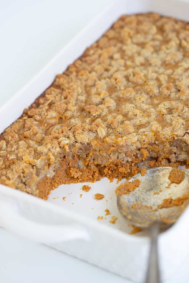 white baking dish with a serving spoon and pumpkin crisp