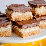 coconut chocolate bars on a white cake plate with a yellow fabric
