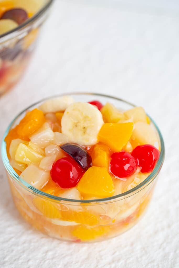 small bowl full of fruit salad on a white background