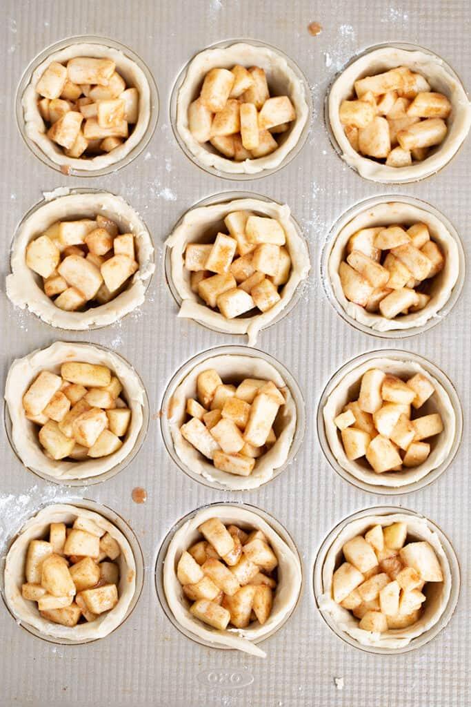 cupcake pan full of pie crust and apple pie filling