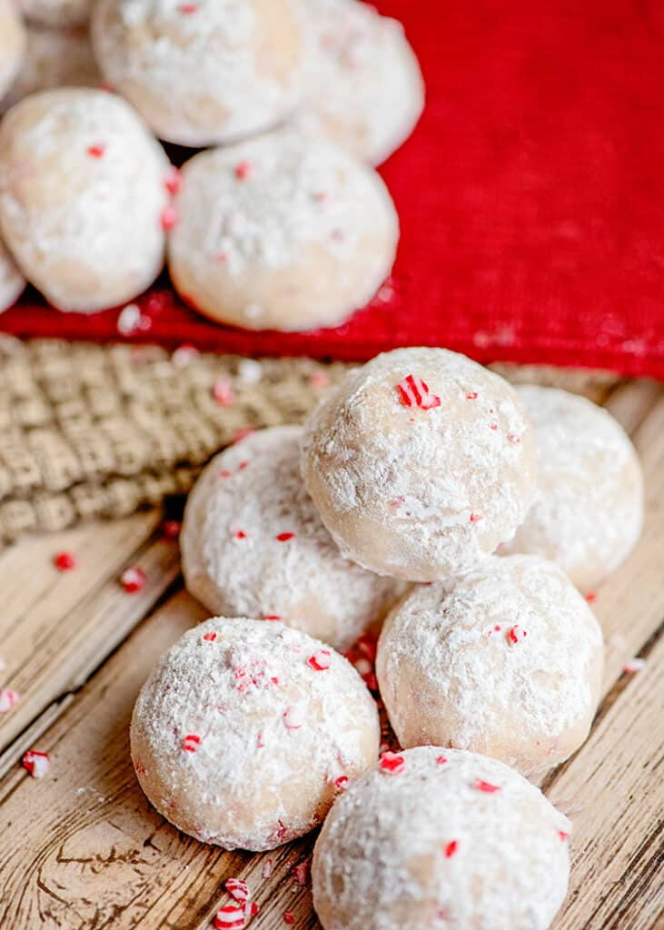 cookies on a wooden surface with a red linen behind the cookies