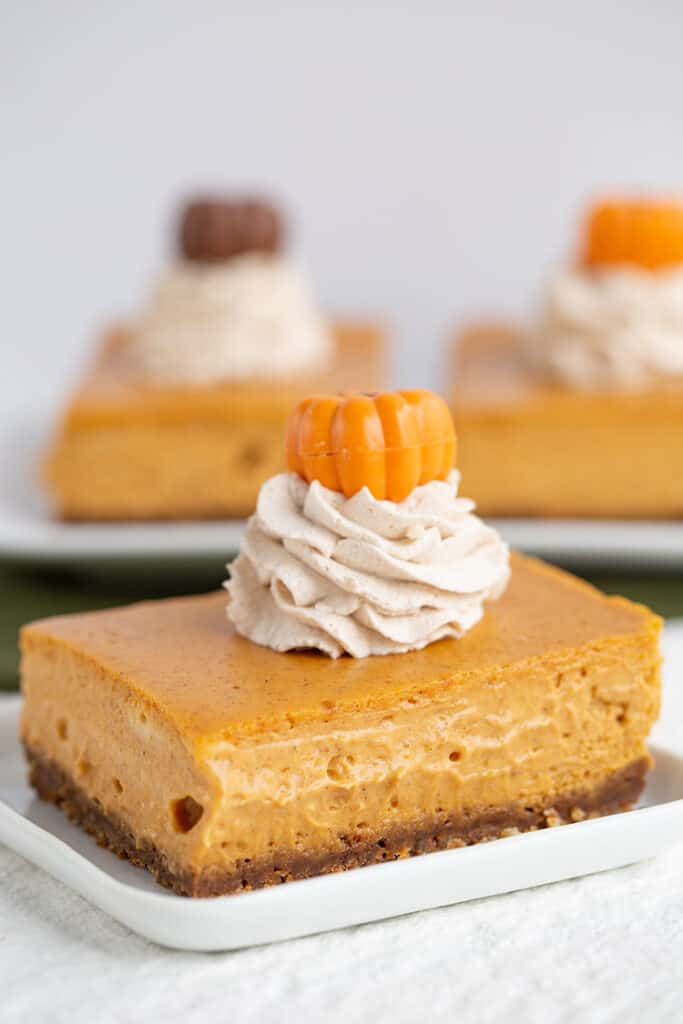 close up of a slice of cheesecake bars with whipped cream and a pumpkin on top