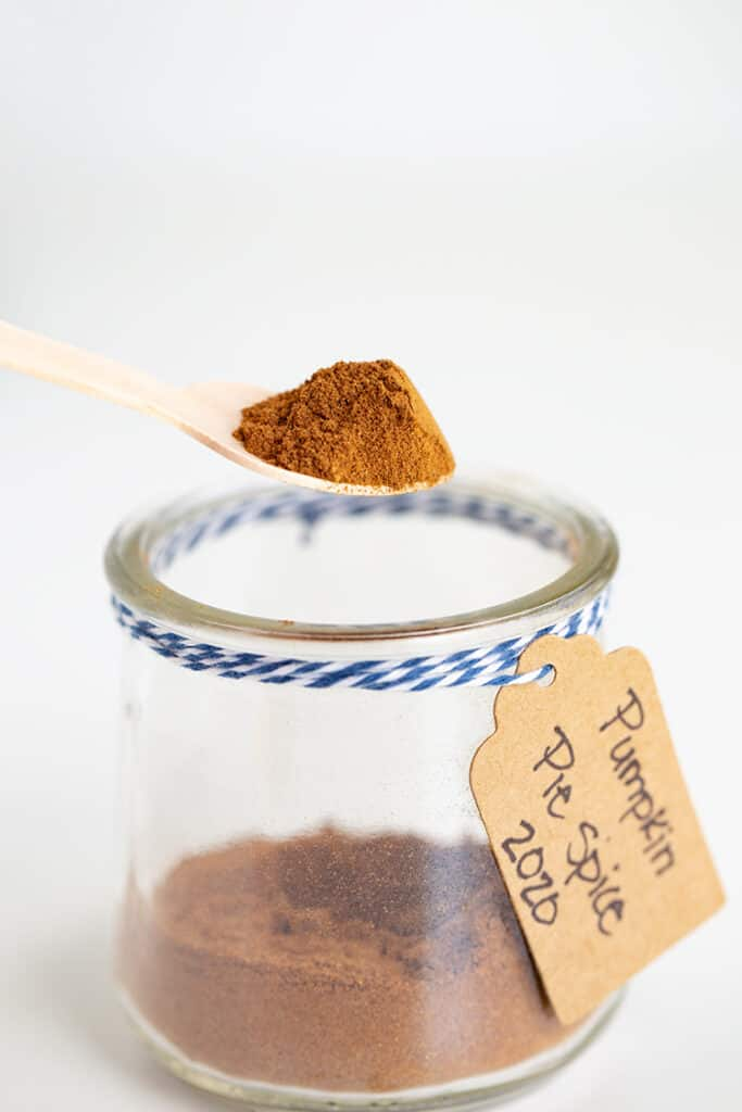 wooden spoon full of pumpkin pie spice above a glass jar of pumpkin pie spice