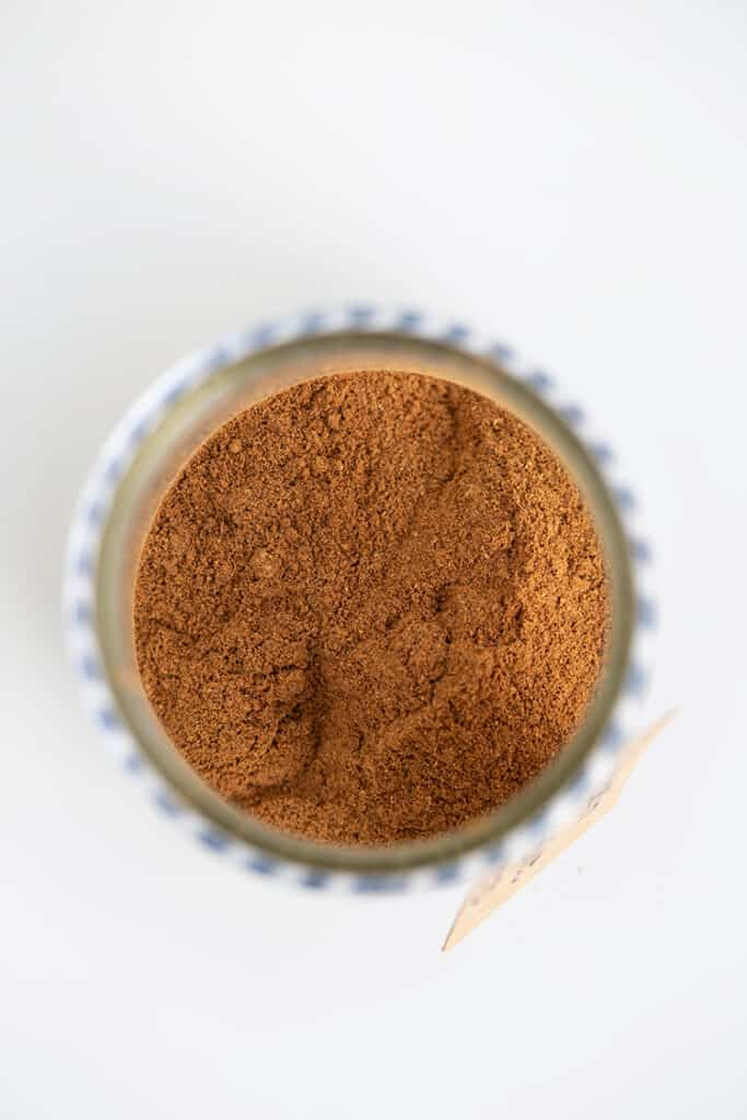 looking straight down into a glass jar to see the spices with a white surface