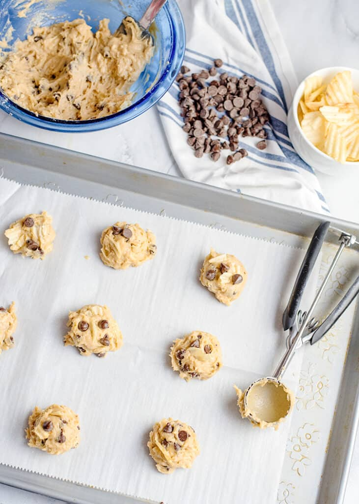 scoops of cookie dough on a piece of parchment paper with a cookie scoop beside it
