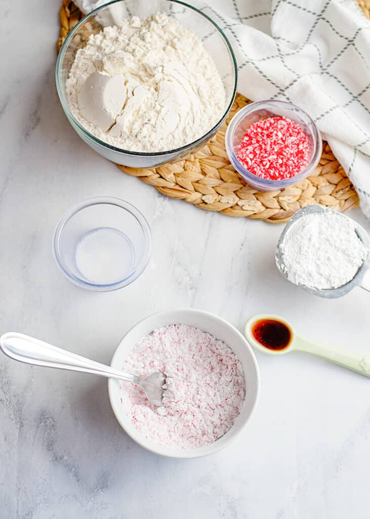 bowl of powdered sugar with the ingredients around it for the snowball cookies