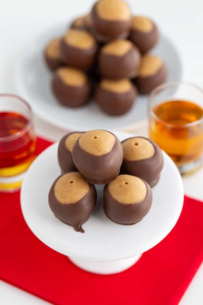 peanut butter balls on a white cupcake stand with a red fabric under the balls
