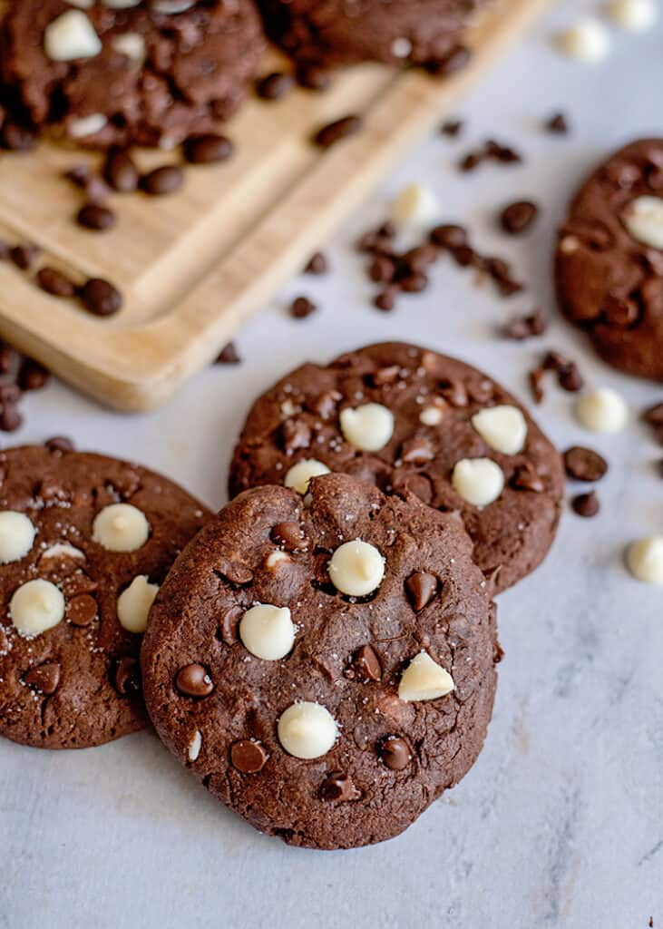 cookies on a marble surface with chocolate chips around them