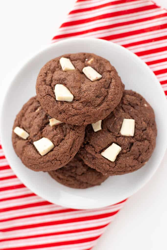 overhead photo of chocolate cookies on a white plate with a striped fabric under it