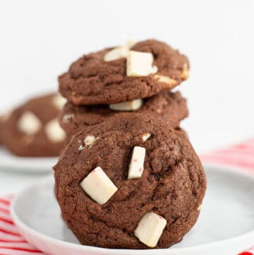 stack of cookies with another cookie leaned on the stack on a white plate with a candy cane striped linen