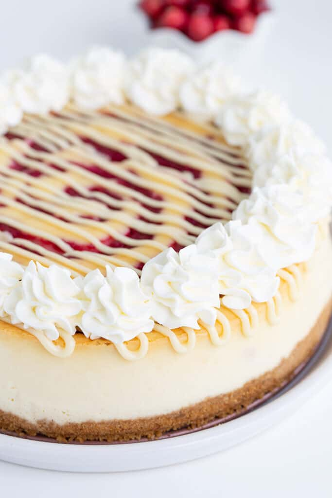 whole cheesecake on a white plate on a white surface with cranberries behind the cheesecake