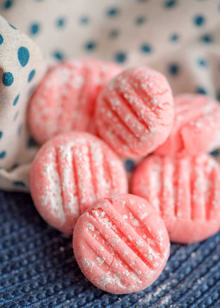pink mints sitting on a blue placemat