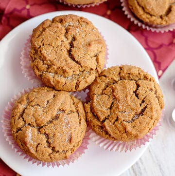 muffins on a white plate with a maroon fabric under the plate