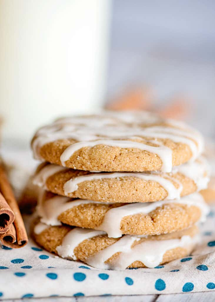 a shot of the side of a stack of cookies with a glass of milk behind it