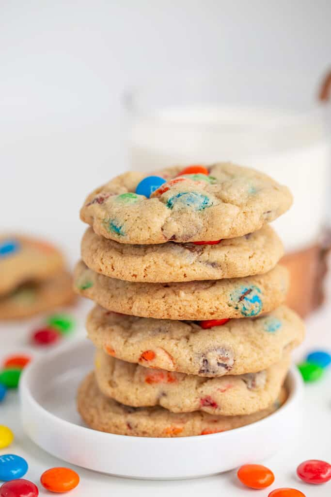 stack of cookies on a small white plate with a mug of milk behind it