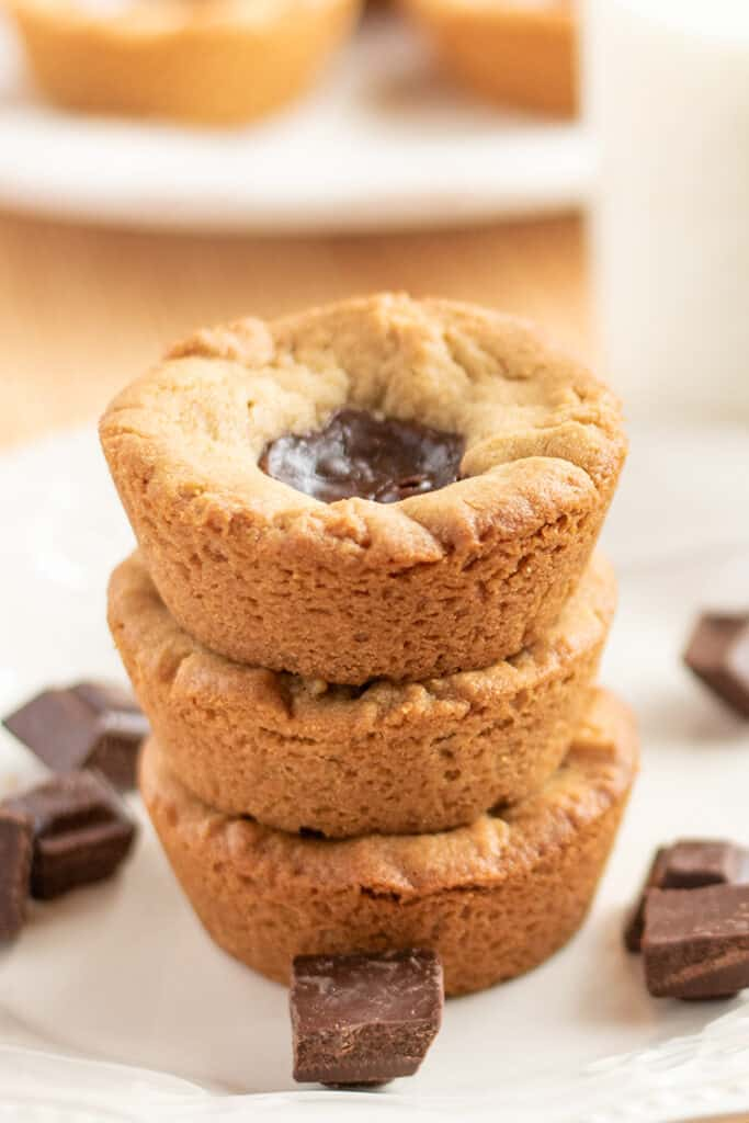 stack of peanut butter cookie cups with pieces of chocolate around it on a white plate