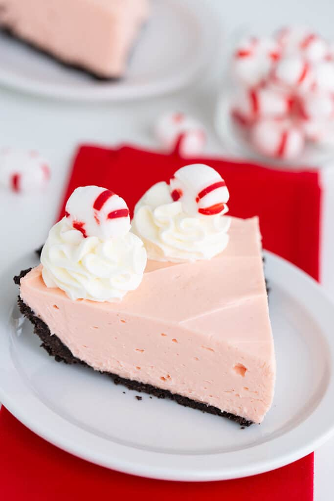 pie on a white dessert plate with a red fabric under the plate and mints behind the plate