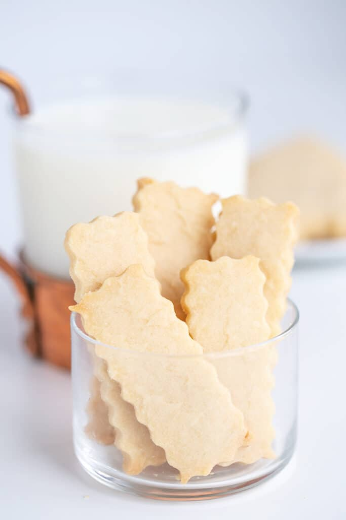 glass bowl with shortbread cookies in it with a glass of milk behind it