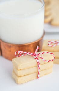 shortbread cookies tied with bakers twin with a glass of milk behind it