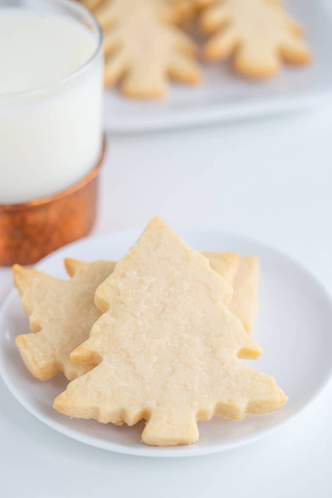 christmas tree cookies on a small white plate with a platter of cookies behind it and a glass of milk