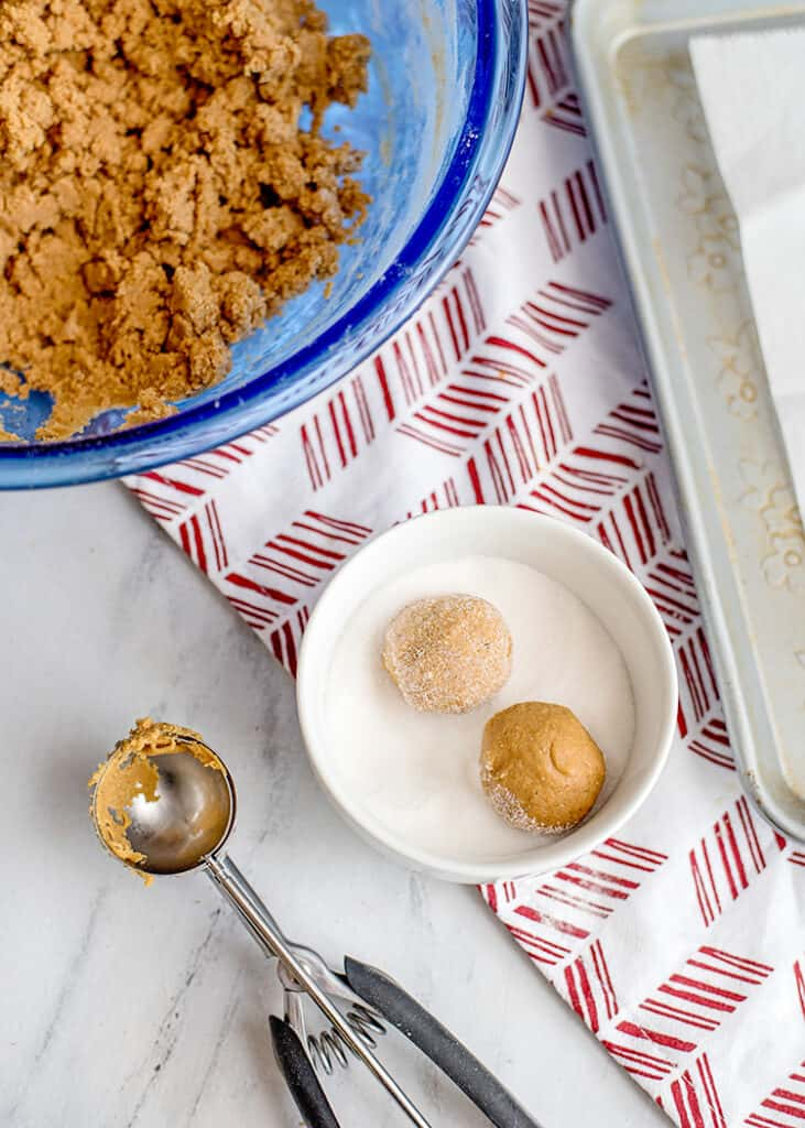 balls of cookie dough in a small bowl of sugar with a cookie scoop next to the bowl