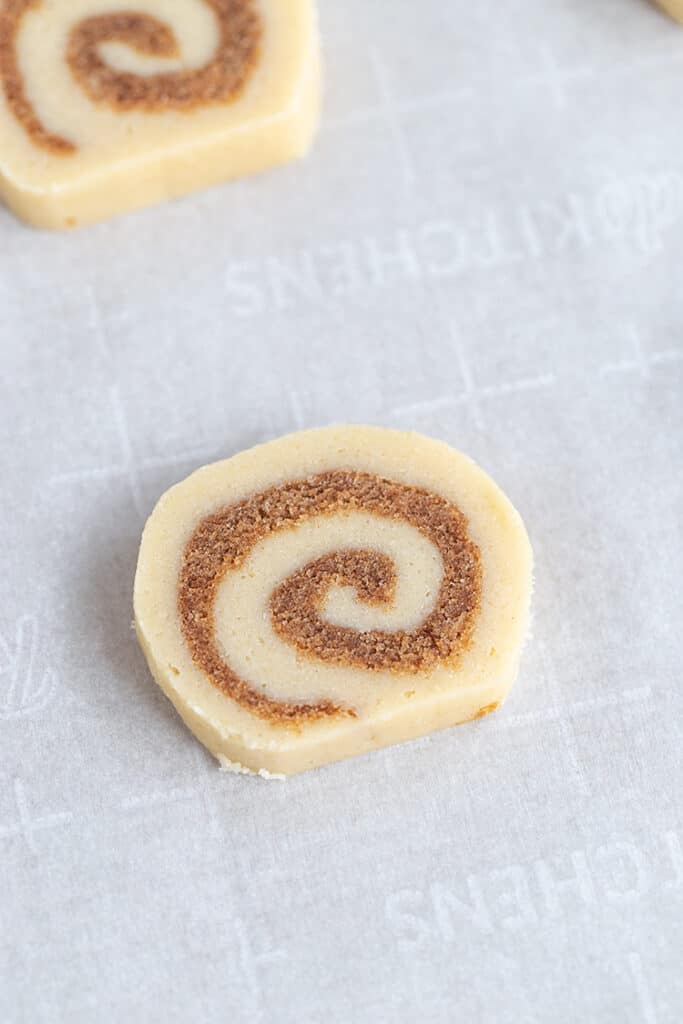 slices of cinnamon roll cookie on a parchment lined cookie sheet