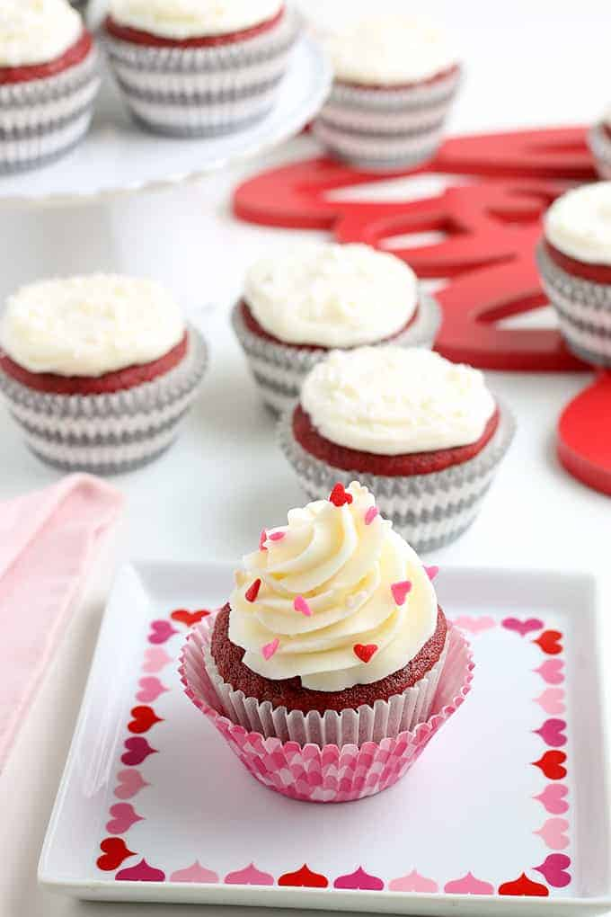 a cupcake on a square plate with hearts on it